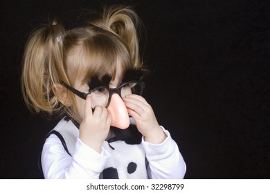 Little girl wearing silly mustache disguise