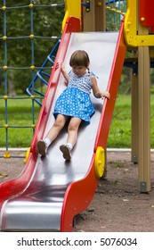 Little girl wearing spotted blue-white dress and braids sliding on children's chute