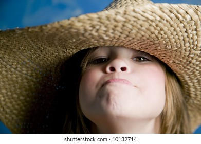 Little girl wearing a straw cowboy hat makes a funny face
