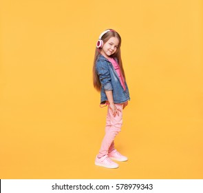 little girl wearing stylish clothes on yellow colorful background