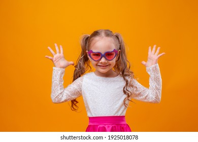 a little girl wearing sunglasses on a yellow background