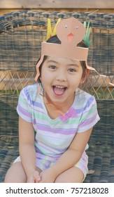 Little girl wearing Thanksgiving turkey artwork from school on her head, filtered tones