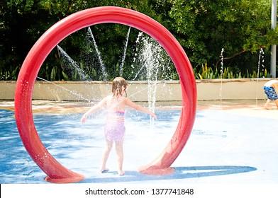 little girl wet at splash pad