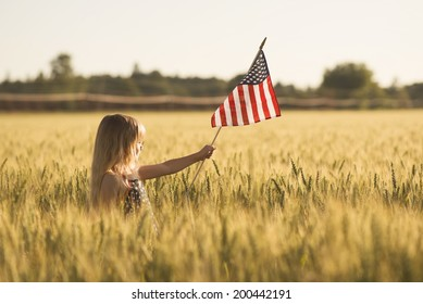 Little girl with wheat field with American flag.