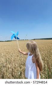 Little girl in wheat field holding wind wheel