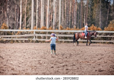 Little girl with whip in hands standing in paddock