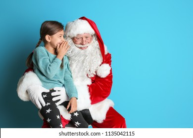 Little girl whispering in authentic Santa Claus' ear on color background