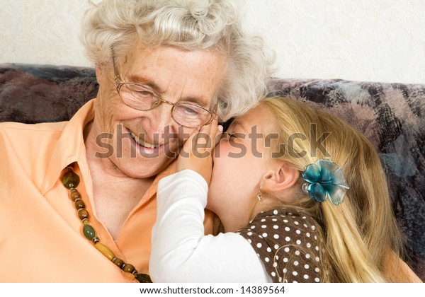 a little girl with is whispering with her great-grandmother