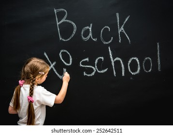 little girl in a white blouse with pigtails writes with chalk on black chalkboard back to school