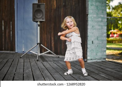 Little girl in white dress dancing at the old wooden stage