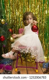 little girl in white dress decoration christmas tree  red balls