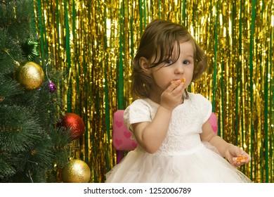 little girl in white dress eat slice mandarin  fruit closeup