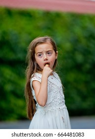 A little girl in a white dress is eating ice cream.