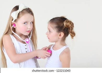 Little girl in white dress listens heartbeat of another girl by toy phonendoscope and looks at camera. Focus on left girl.