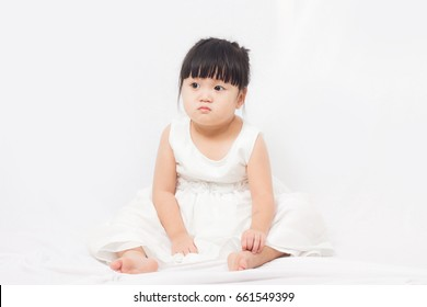 Little girl in white dress making funny face on a white background.