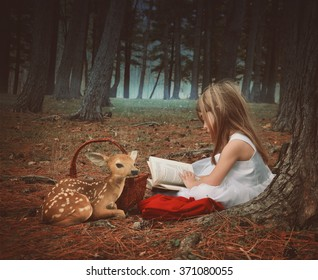 A little girl in a white dress is reading on old story book with a baby deer in the dark woods for an education or imagination concept.