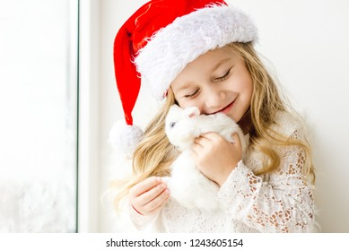 little girl in white dress with a little girl in red dress sitting by the window waiting for Christmas and Santa Claus