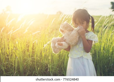 Little girl in white dress standing bear teddy bear. Amid green meadows Have sunlight