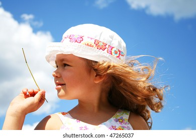 Little girl in white hat with the sky as background