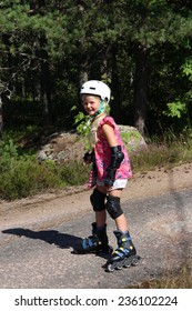 Little girl with white helmet on her head rollerblades down hill in protective gear
