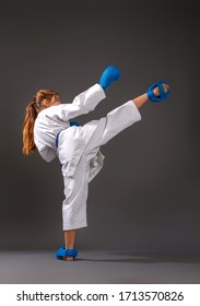 Little girl in a white kimono with a blue belt and equipment carries out blows on a dark background
