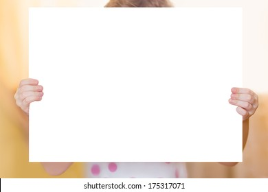 Little girl with white paper in hands.