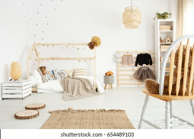 Little girl in white scandinavian bedroom with eco-friendly accessories