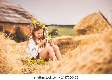 LIttle girl in white shirt sitting on a haystack and making a flower wreath