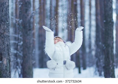 a little girl in a white suit in the winter woods catches the snow