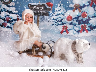 A little girl is in a white winter wonderland setup with snow trees and Christmas snow bear props sitting on sled
