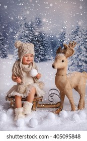 A little girl is in a white winter wonderland setup with snow  and Christmas deer props sitting on sled
