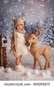 A little girl is in a white winter wonderland setup with snow  and Christmas deer props