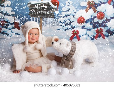 A little girl is in a white winter wonderland setup with snow trees and Christmas snow bear props sitting on snow