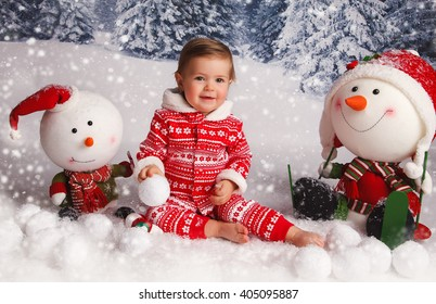 A little girl is in a white winter wonderland setup with snow trees and Christmas snowman  props sitting on the ground
