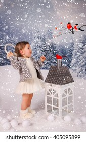A little girl is in a white winter wonderland setup with snow  and Christmas house props standing and smiling looking at bullfinches