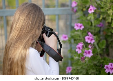 Little girl who is photographing some flowers