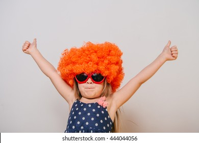 little girl in a wig. orange wig. funny little girl in a dress, glasses and an orange wig. girl dressed in a dress and a wig. wig and glasses. Girl shows gesture thumbs up