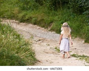 little girl in wild flowers wreath walking on road barefoot