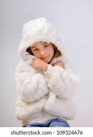 Little girl with a winter coat, isolated on white