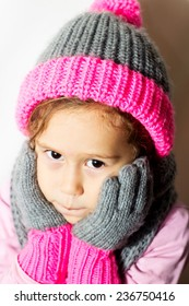 Little girl in winter hat with gloves and scarf on a white background.