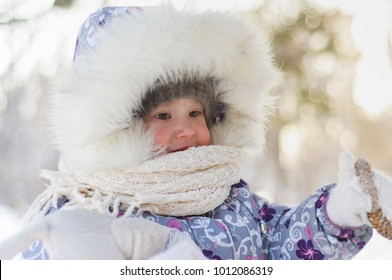 Little girl in winter Park in cold Sunny day