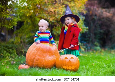 Little girl in witch costume and baby boy in huge pumpkin playing in autumn park. Kids at Halloween trick or treat. Toddler with jack-o-lantern. Children with candy bucket in forest.