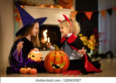 Little girl in witch costume and boy dressed up as vampire on Halloween trick or treat. Children trick or treating with candy bucket. Kids celebrate Halloween at fireplace with pumpkin and lantern.
