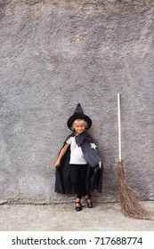 A little girl in a witch costume is playing and having fun on  a broom