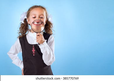Little Girl Without Teeth Holding A Magnifying Glass Isolated On Blue Background