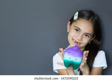 little girl without two front teeth laughs while looking at the camera and holding a toy tooth. Lost tooth, loss of milk tooth