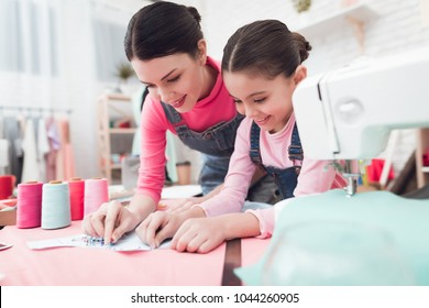 A little girl and woman together construct clothes. They are with Mom in the sewing workshop. They are in a good mood. They use pins.