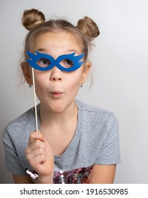 Little girl with wondered facial expression in paper eyeglasses masquerade mask studio portrait. Amazed female child with surprise on face. Overjoyed kid wearing beautiful masque. Carnival costume