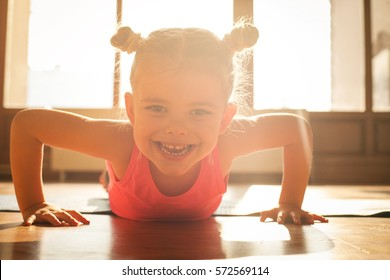 Little girl workout at home. Looking at camera.