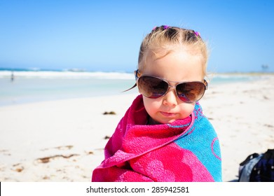 Little girl wrapped in a colorful beach towel and wearing sunglasses sitting at the ocean beach